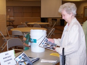 Helen Conway helped sell calendars at the Fall Fling. A portable water filter is in the background