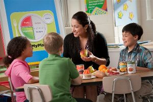 A nutrition educator shares a lesson with three elementary school students.