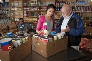 A volunteer helps a food pantry client fill his box with essential items.